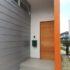 鋼板横葺きの外壁と無垢板の玄関扉